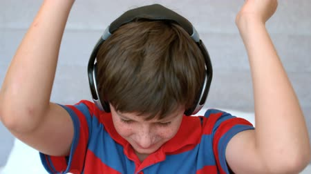 menino : Young boy enjoying music with headphones in slow motion at 250 frames per second Vídeos