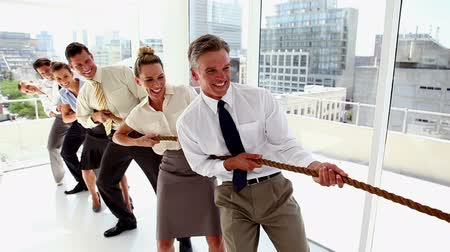 тянущий : Business people pulling a rope together with motivation in the office