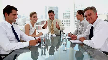 pozitivní : Laughing businessman giving thumbs up with colleagues around in a meeting room
