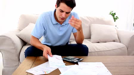 banknoty : Man stressed with so many bills to pay in his living room