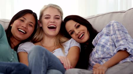 смеющийся : Three friends laughing together while watching television on the couch