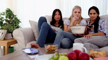 смеющийся : Friends eating popcorn while watching a movie in the living room