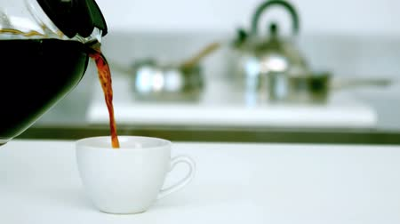 kawa filiżanka : Black coffee being poured into cup of coffee in the kitchen