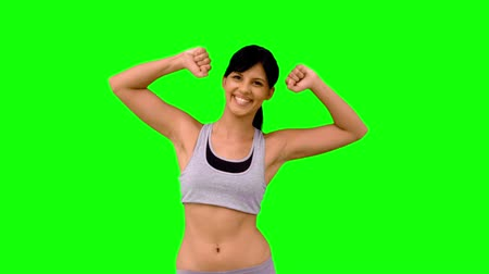 abs : Athletic woman tensing her arms on green screen  in slow motion