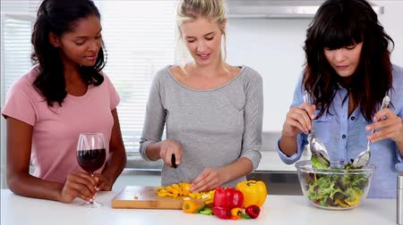 food preparation : Attractive friends preparing salad in the kitchen while one friend is holding a glass of red wine