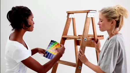swatches : Friends wondering what colour choose for the wall using a colour chart Stock Footage