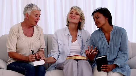 dua eden : Three mature friends praying together with bibles on the couch