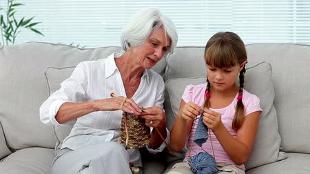 внучка : Granny teaching her granddaughter how to knit at home on the couch