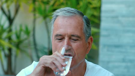 içme : Retired man drinking water outside in slow motion