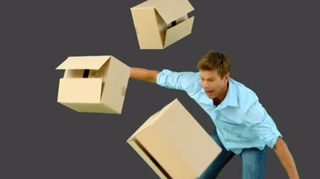 transportar : Clumsy man dropping boxes over on grey screen in slow motion