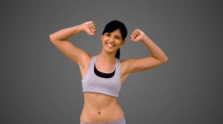 abs : Fit brunette showing her arm muscles on grey background in slow motion