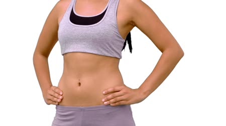abs : Fit woman turning to camera on white background in slow motion