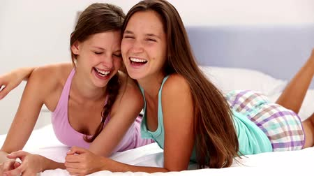 quarto doméstico : Girls embracing and smiling at camera lying on bed