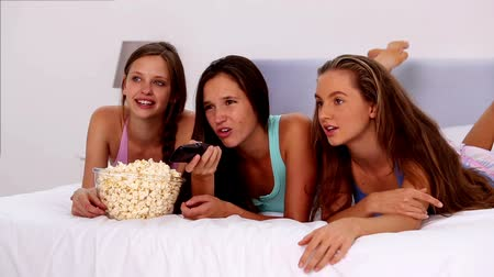 ležící : Friends eating popcorn and watching tv on bed in their pajamas
