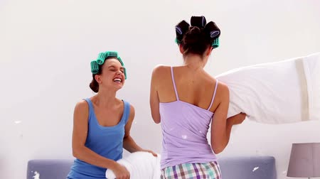 pizsama : Friends in hair rollers having pillow fight at home at slumber party Stock mozgókép