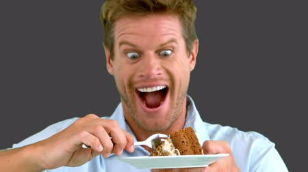 tongue out : Attractive man about to eat a cake on grey screen in slow motion