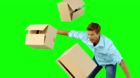 deslizamento : Clumsy man dropping boxes over on green screen in slow motion Vídeos