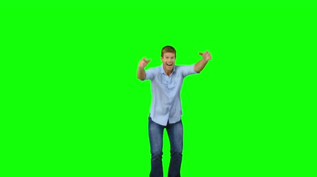 salto : Man jumping to show his triumph on green screen in slow motion Stock Footage
