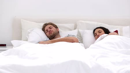 adormecido : Couple sleeping peacfully with partner pressing snooze on alarm clock at home in bedroom Vídeos