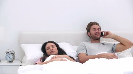adormecido : Man talking on phone while his partner is sleeping in bed at home