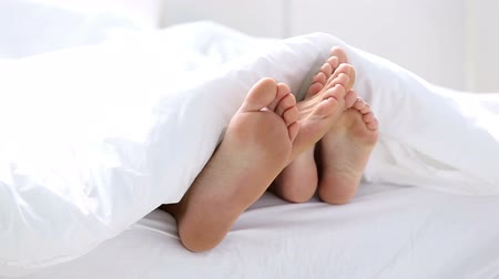 kobiece stopy : Pair of feet playing footsie under the covers at home in bed Wideo