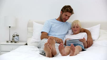 otec : Father and son using tablet together at home on bed