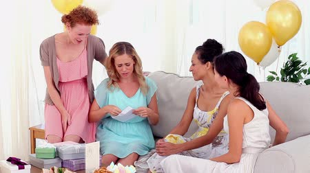 receber : Friends having a party and giving their friend a card at home on the couch Stock Footage
