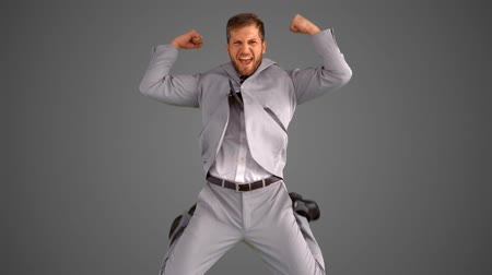 ceket : Succesful businessman leaping on grey background in slow motion