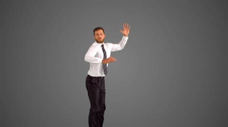 leaping : Businessman leaping up and grabbing legs on grey background in slow motion