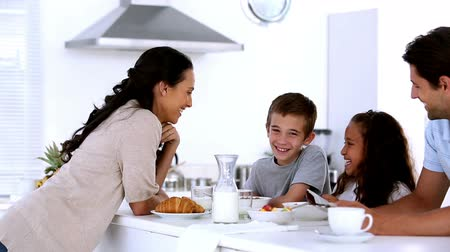 kahvaltı : Mother chatting to children at family breakfast at home in kitchen