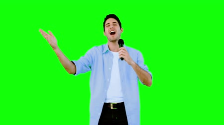 śpiew : Man singing into microphone on green screen in slow motion