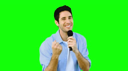 mikrofon : Man singing into microphone with emotion on green screen in slow motion