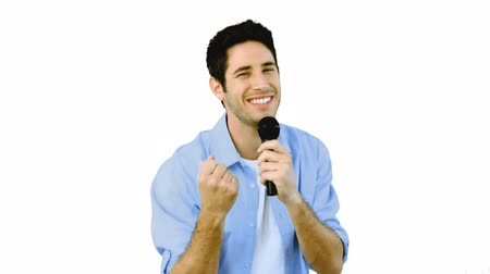 karaoke : Man singing into microphone with emotion on white background in slow motion Stock Footage