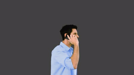 telefone celular : Angry man talking on phone and throwing it away on grey background in slow motion