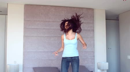 jump : Pretty brunette jumping on her bed in slow motion