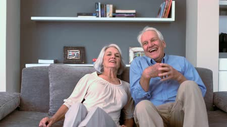 emekli : Retired couple flopping down on the couch in slow motion Stok Video