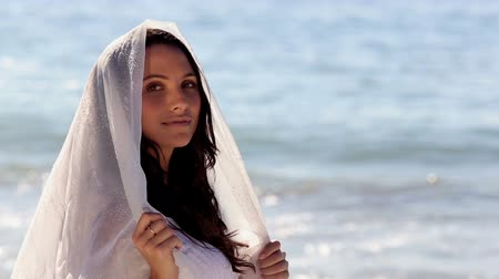 ношение : Attractive woman looking at the sea and wearing scarf