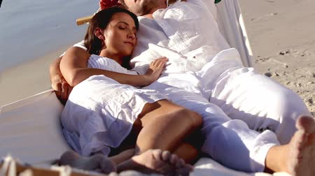 vacation : Attractive couple sleeping together in a hammock on a sunny beach