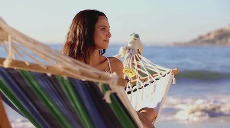 strand : Cute woman holding a cocktail in a hammock on a sunny beach