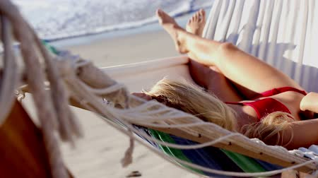 гамак : Attractive woman in red bikini in a hammock on a sunny beach