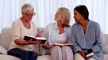 evangélium : Retired friends studying the bible together at home on the couch