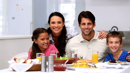 vacsora : Family smiling and waving at the dinner table at home