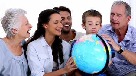 учение : Extended family looking at globe together at home on sofa