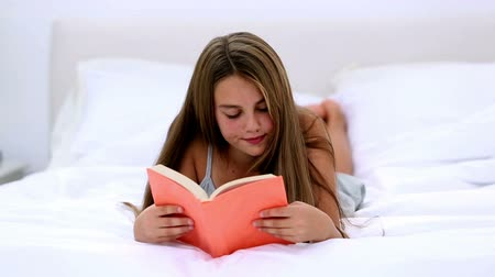 quarto doméstico : Cute girl lying on bed and reading at home in bedroom