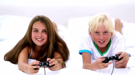 rodzeństwo : Siblings playing video games together at home on bed Wideo
