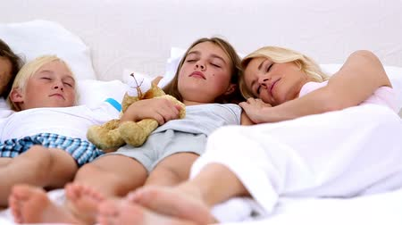 сестра : Parents dozing with their children at home in bedroom