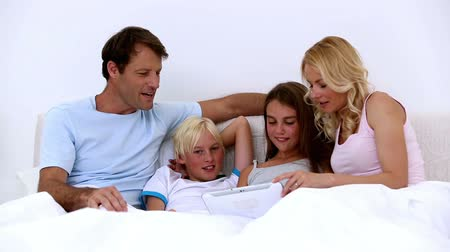 müzakere : Cute family using tablet together at home in bed Stok Video