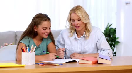 házi feladat : Mother and daughter doing homework together at desk in living room