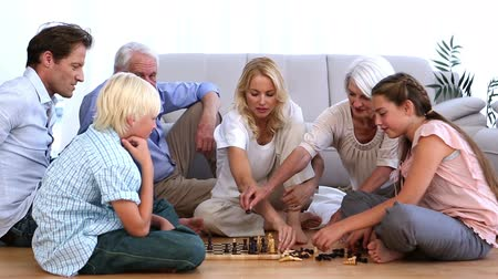 family life : Extended family playing chess at home on sitting room floor Stock Footage