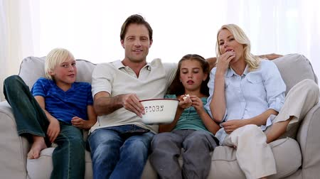 family life : Famil watching tv and eating popcorn at home on the couch
